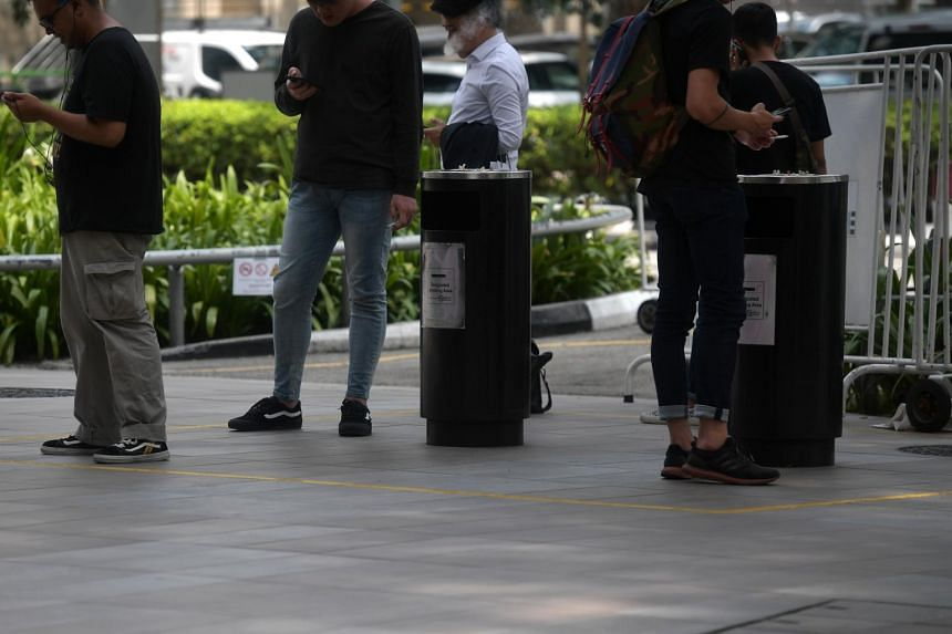 Smokers near a rubbish bin in front of Cathay Cineleisure Orchard.
