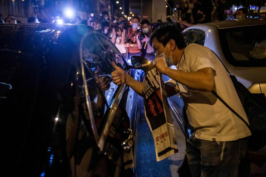 Supporters holding copies of the Apple Daily newspaper as media mogul Jimmy Lai was released on bail on Wednesday in Hong Kong. PHOTO: AGENCE FRANCE-PRESSE