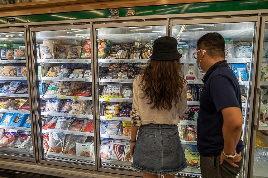 Customers shopping for frozen food at a store specialising in imported goods in Beijing yesterday. China recently reported finding the coronavirus on frozen chicken wings from Brazil, where the pandemic is raging, and on the outer packaging of frozen
