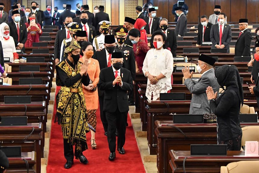 Indonesian President Joko Widodo - dressed in a traditional outfit from East Nusa Tenggara - and Vice-President Ma'ruf Amin greeting assembly and House members before Mr Joko's state of the union address in Parliament in Jakarta yesterday. PHOTO: AGE