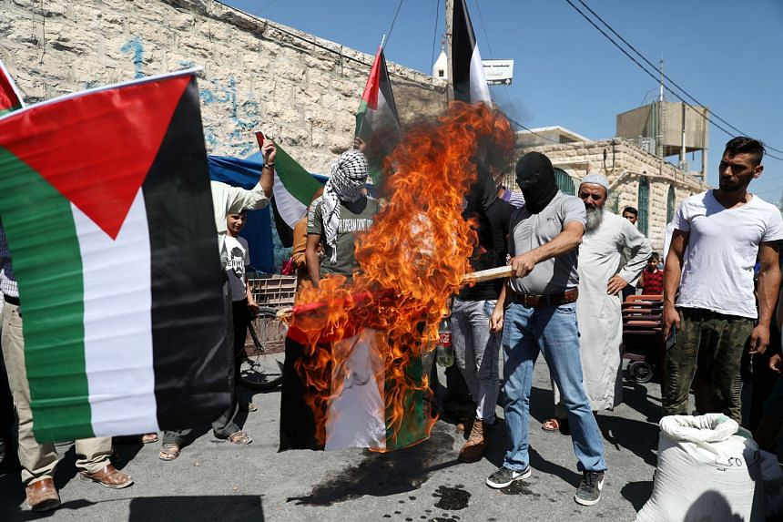 WEST BANK Palestinian protesters burning a United Arab Emirates flag yesterday in the city of Yatta in Hebron district. The Palestinian Authority has condemned the deal between Israel and the UAE as a betrayal of the Palestinian people.