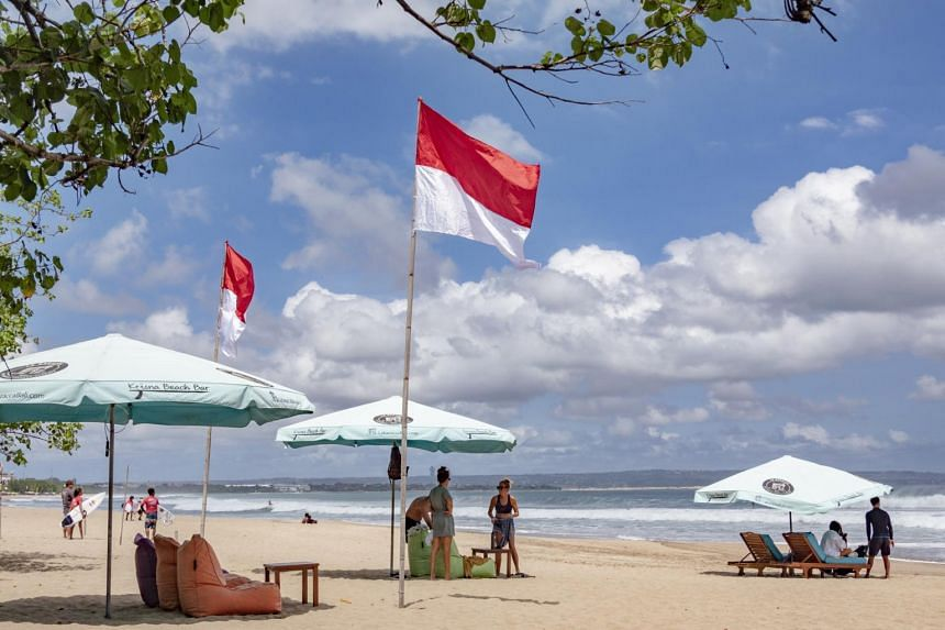 Tourists relax at a beach in Seminyak, Bali, on Aug 7, 2020.