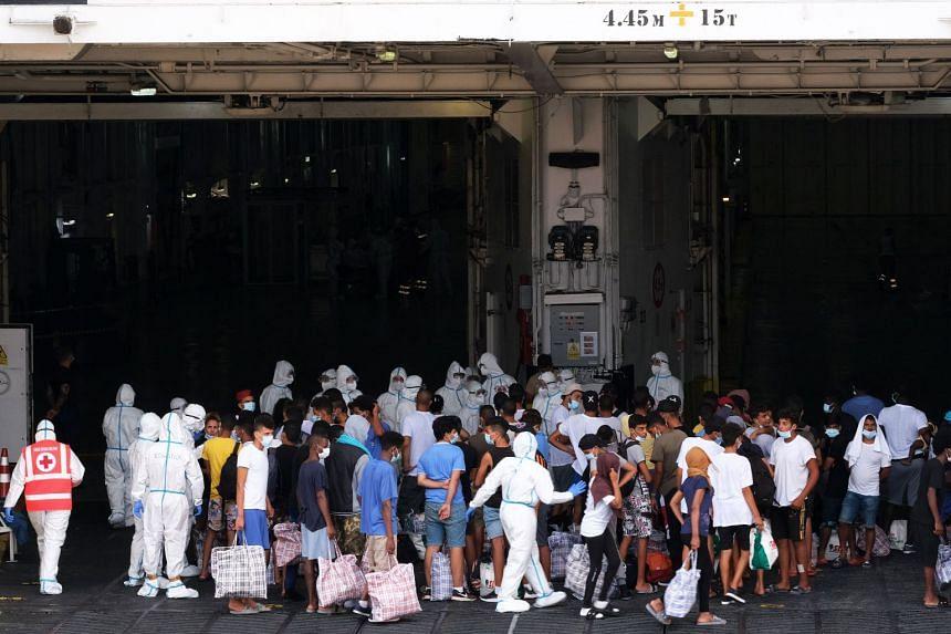 Migrants board a coronavirus quarantine ship docked at the Italian Pelagie Island of Lampedusa on Aug 4, 2020.