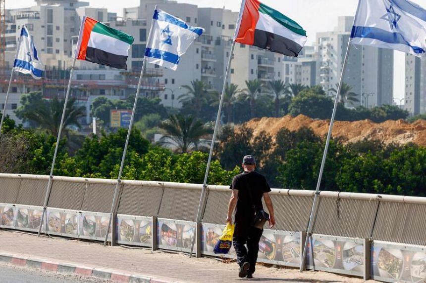 A man walks beneath Israeli and United Arab Emirates flags lining a road in the Israeli coastal city of Netanya, on Aug 16, 2020.