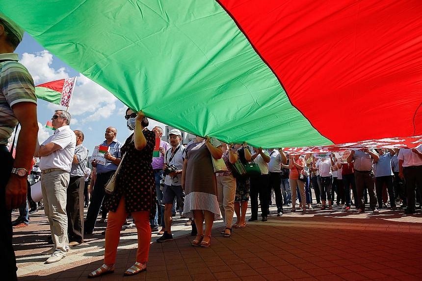 Supporters of Mr Lukashenko holding a large national flag as they took part in a rally in Minsk yesterday. A Reuters reporter estimated that around 5,000 people attended the protest, while the Belarusian Interior Ministry put the number at 65,000.