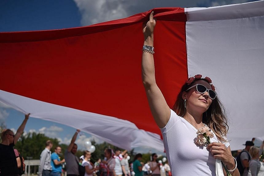 Demonstrators carrying a former white-red-white flag of Belarus, used in opposition to the government, as they protested in central Minsk yesterday against President Alexander Lukashenko's re-election. A Reuters reporter said the rally was huge, with