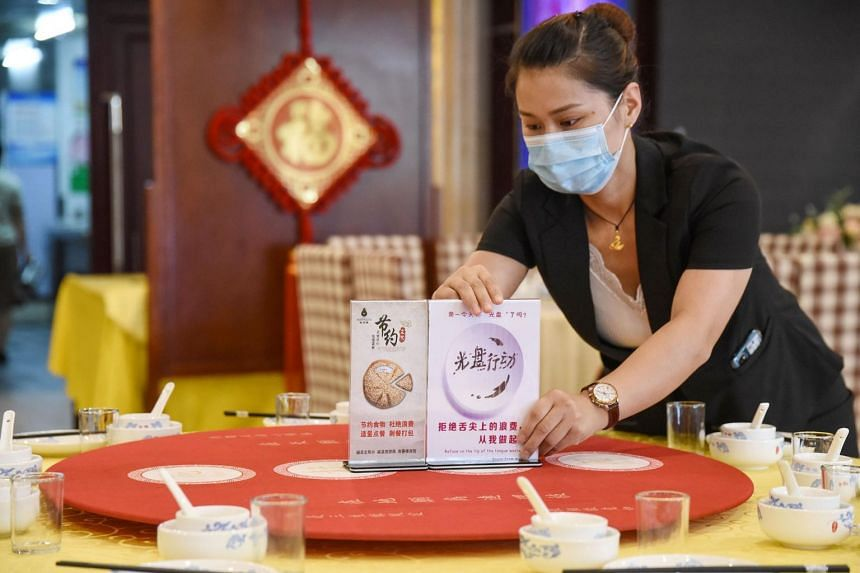 A staff member sets up signs encouraging people not to waste food at a restaurant in Handan, China, on Aug 13, 2020.