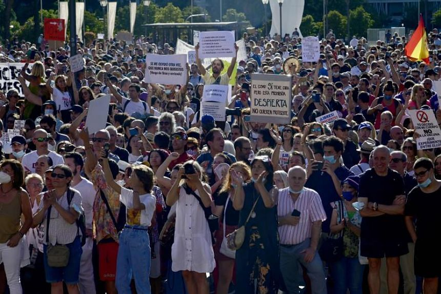 People gather holding signs and shouting slogans during a protest against Covid-19 measures in Madrid, on Aug 16, 2020.