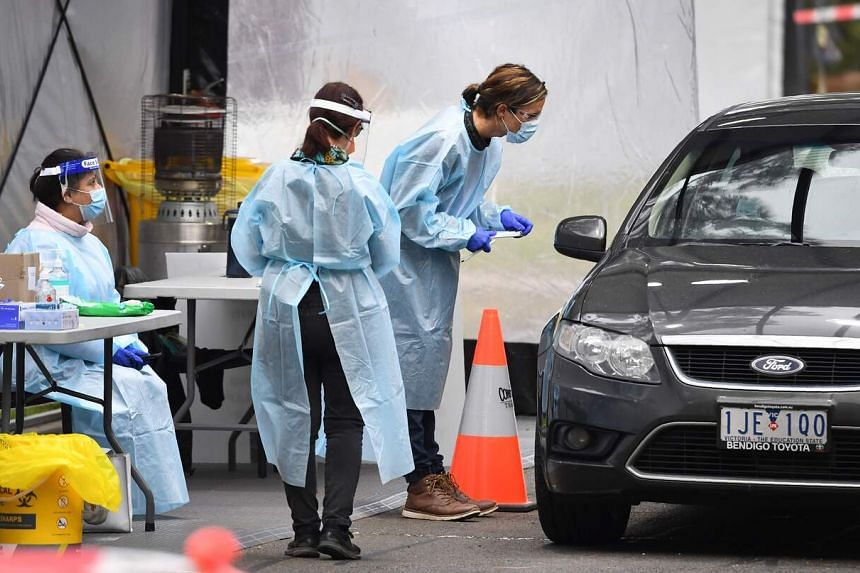 Medical staff prepare to take a swab at a drive-through testing clinic in Melbourne, on Aug 13, 2020.