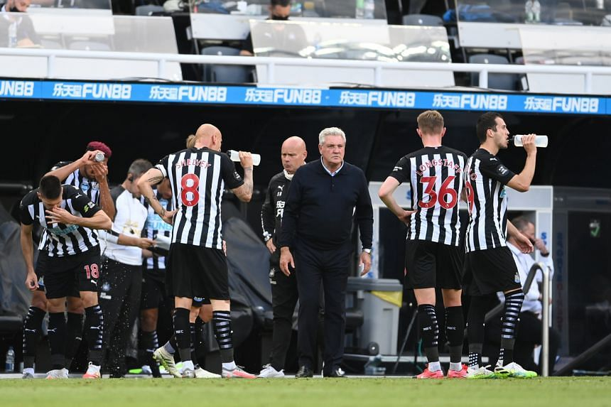 Newcastle United manager Steve Bruce speaks with players during a drink break on July 26, 2020.