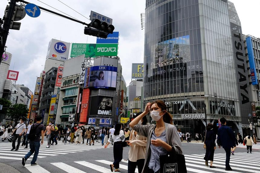 People wearing face masks walk across the Shibuya Crossing in Tokyo, on May 31, 2020.