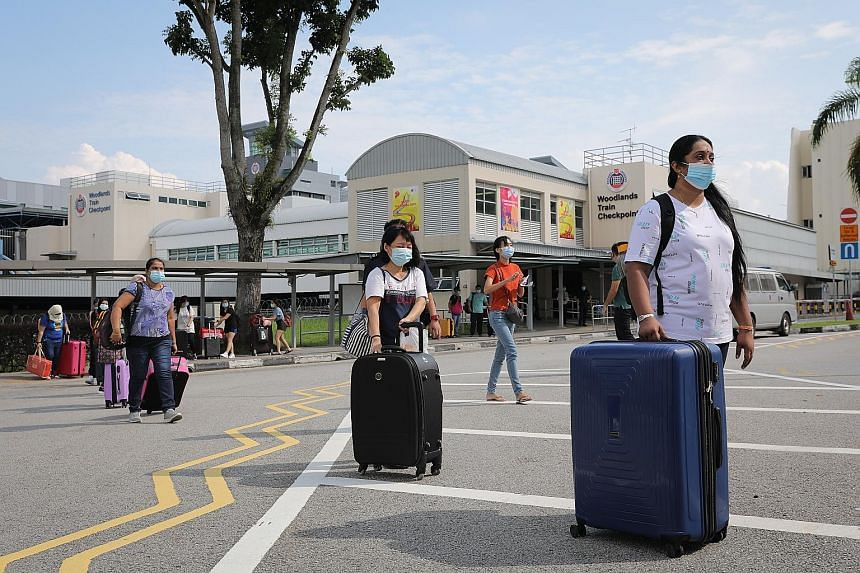 People from Malaysia arriving in Singapore yesterday at the Woodlands Train Checkpoint. As at 10am yesterday, about 300 people had crossed the border in both directions, said a Malaysian official. People arriving in Singapore from Malaysia yesterday,