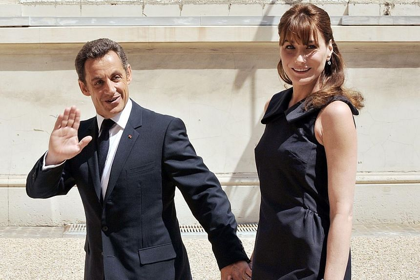 Mr Nicolas Sarkozy and his wife Carla Bruni in Paris on Bastille Day in this July 2008 photograph. He married singer and former model Bruni after a whirlwind romance.
