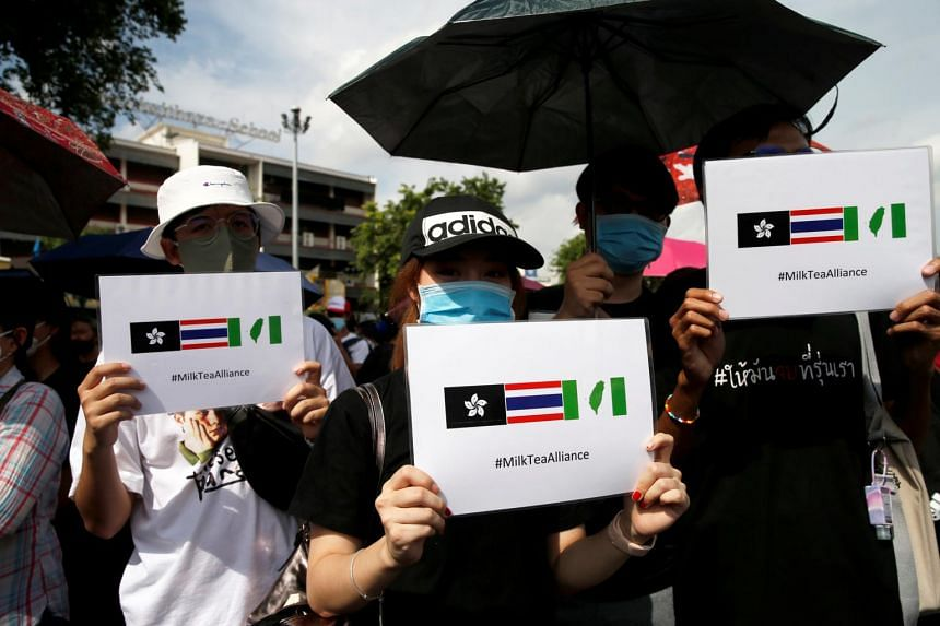 Protesters hold signs of the Milk Tea Alliance during a rally in Bangkok on Aug 16, 2020.