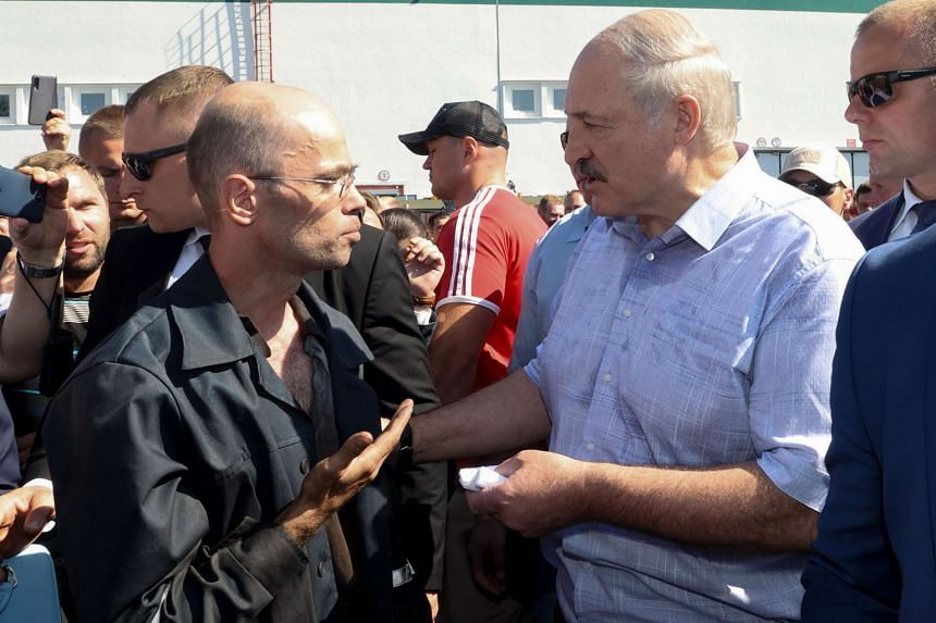 President Alexander Lukashenko (in light-coloured shirt) speaking to a worker at the Minsk Wheel Tractor Plant in the capital yesterday, amid mass protests and strikes as well as calls for him to step down. Pro-opposition Belarusians rallying in Mins