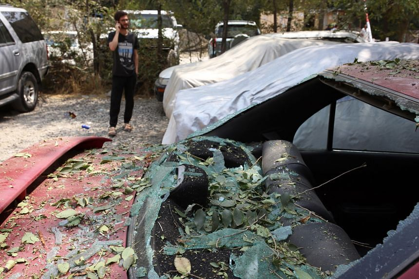 A damaged car is seen after a rocket attack in Kabul on Aug 18, 2020.