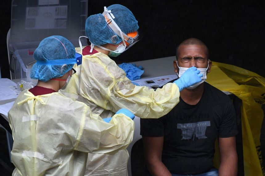 An April 2020 photo shows a migrant worker undergoing a nasal swab test at a domitory in Singapore.