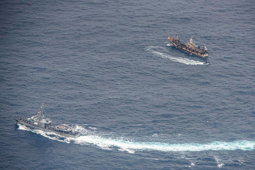 In a photo from Aug 7, 2020, Ecuadorian Navy vessels surround a fishing boat near the Galapagos Islands.
