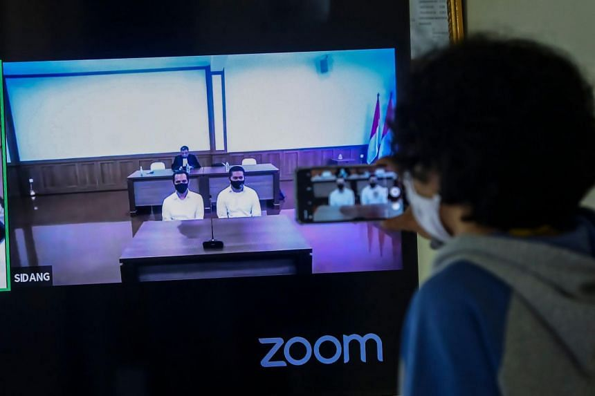 A man watches the video conference of the trial of the two policemen accused for the 2017 acid attack to investigator Novel Baswedan, in Jakarta, on July 16, 2020.
