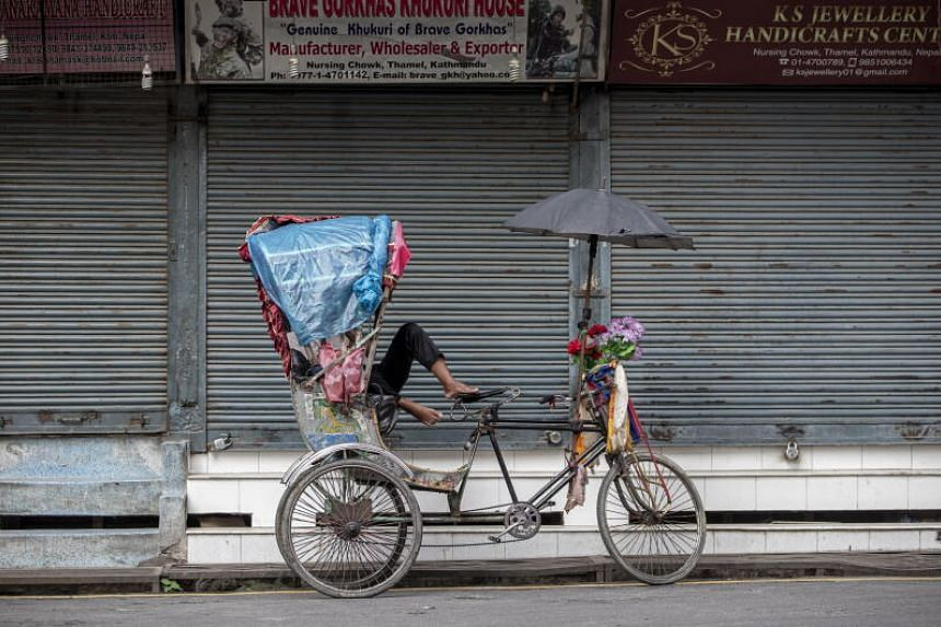 A rickshaw puller rests in front of a closed market in Thamel, Kathmandu, on Aug 17, 2020.