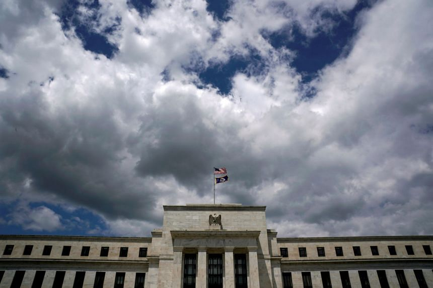Flags fly over the Federal Reserve headquarters on a windy day in Washington.
