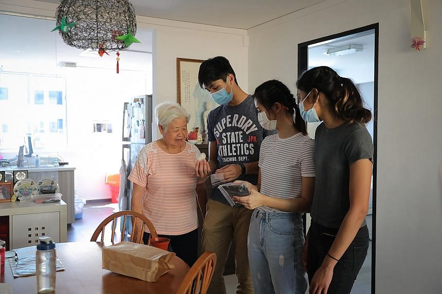 Madam Tay Yoke Mooi, a Fengshan resident, was among the seniors visited on Monday by (from left) junior college graduates Kampton Kam, Maxine Cassandra Lau and Grace Shani Anthony. The three 19-year-olds are working with The Salvation Army on their i
