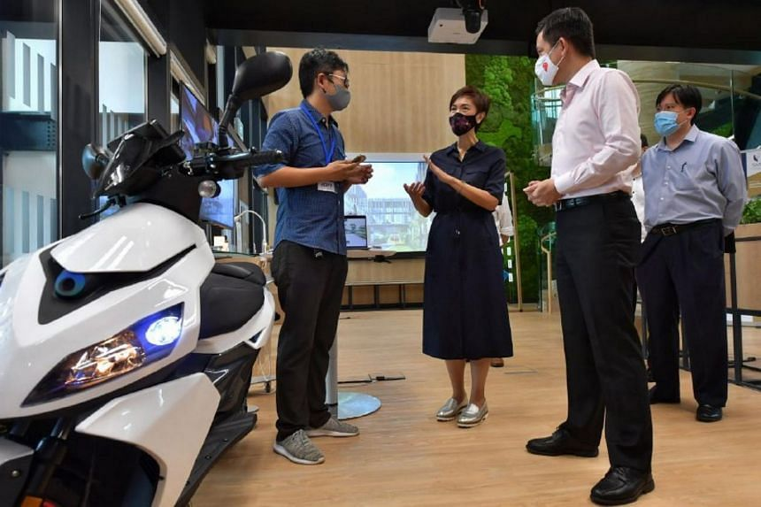 Mr Chan Chun Sing (second from right) and Mrs Josephine Teo (third from right) speaking to Mr James Chan (left), founder of Ion Mobility, on Aug 19, 2020.