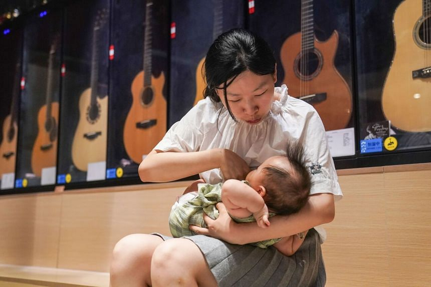 Ms Wang Chao feeding her child at her guitar store in Shanghai, on Aug 5, 2020.