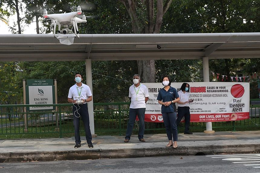 Senior Minister of State for Communications and Information Sim Ann, who is an MP for Holland-Bukit Timah GRC, observing an NEA team operating a drone to detect the presence of stagnant water that may lead to mosquito breeding. The NEA has been deplo