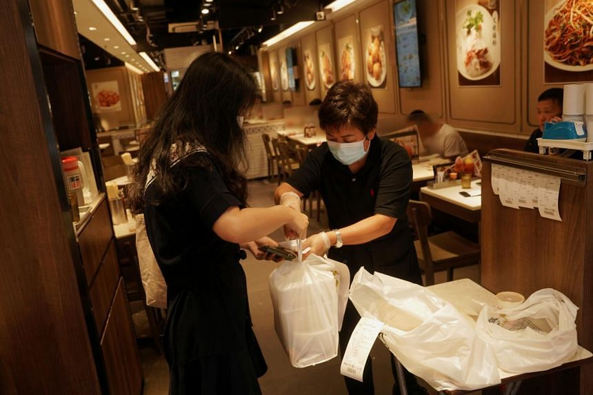 A staff member hands takeaway food to a customer at a restaurant in Hong Kong, on July 20, 2020.