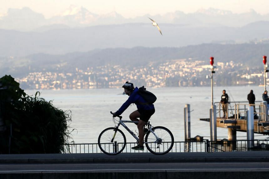 A man cycles along the banks of Lake Zurich in Switzerland, on Aug 6, 2020.