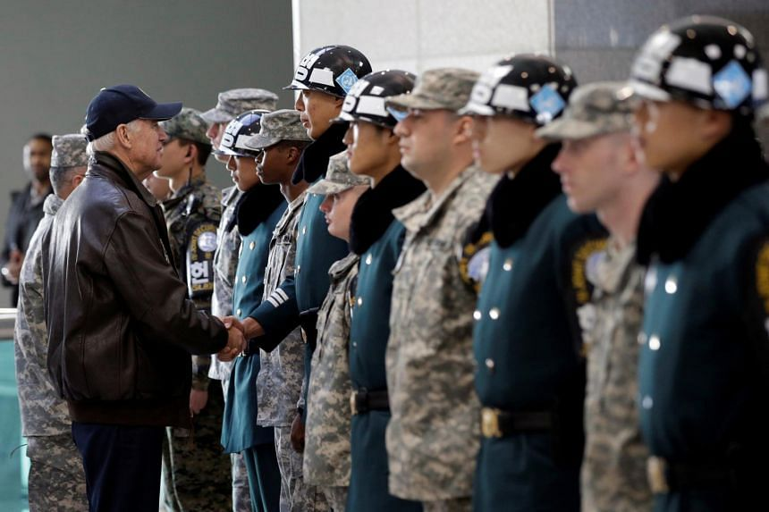In a photo taken on Dec 7, 2013, Mr Joe Biden (front, left) shakes hands with South Korean and US soldiers during a tour of the Demilitarized Zone in Panmunjom.