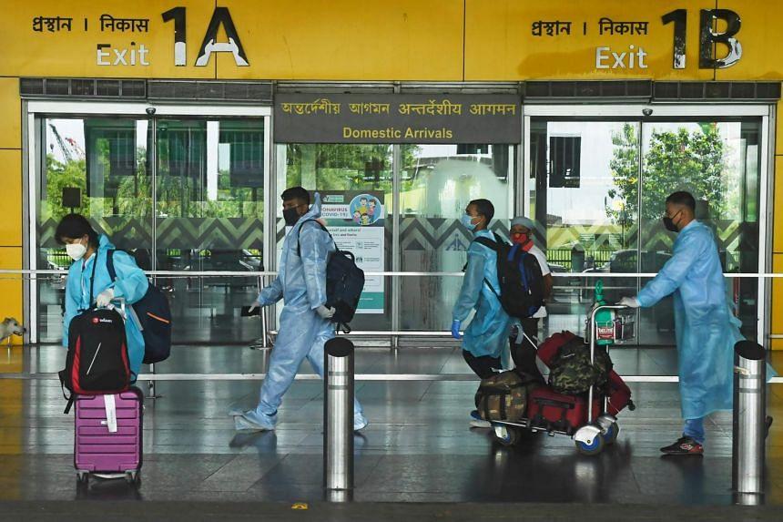 Passengers walk out of the arrival lounge of the Netaji Subhas Chandra Bose International Airport in Kolkata on July 6, 2020.