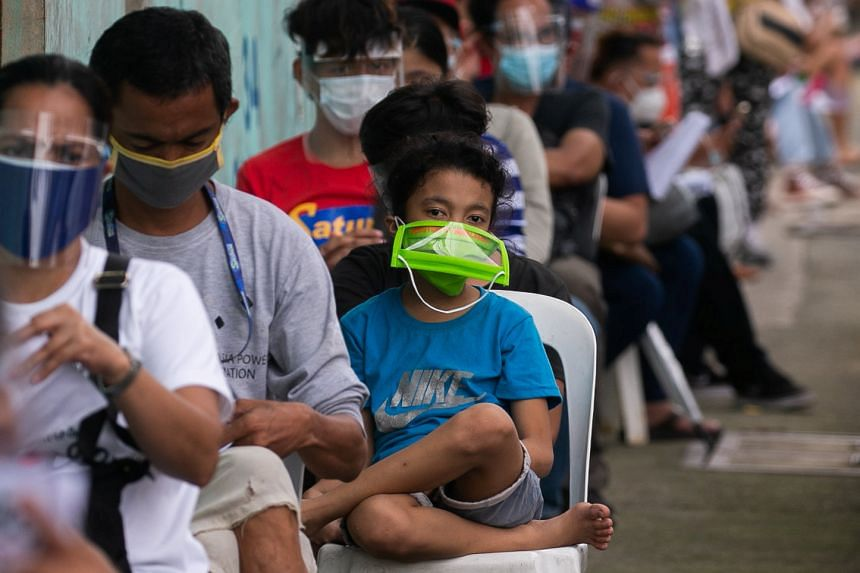A child wears a mask as people wait to be tested for coronavirus at a government facility in the Philippines.
