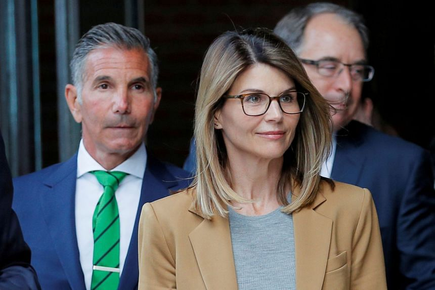 Lori Loughlin and her husband, fashion designer Mossimo Giannulli, leave court in April 2019.