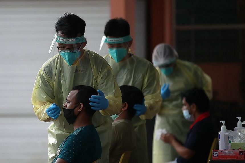 Medical staff conducting a routine swab test for migrant workers in Westlite Juniper dormitory on Tuesday. Recent cases of Covid-19 among foreign workers are being picked up now because the workers are reaching the end of their quarantine periods and