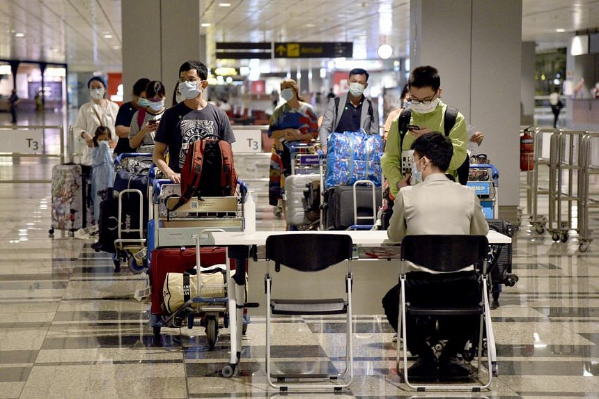 Aviation security staff at Changi Airport Terminal 3 arrival hall assign Singaporeans hotels for them to serve their stay-home notices on May 10, 2020.