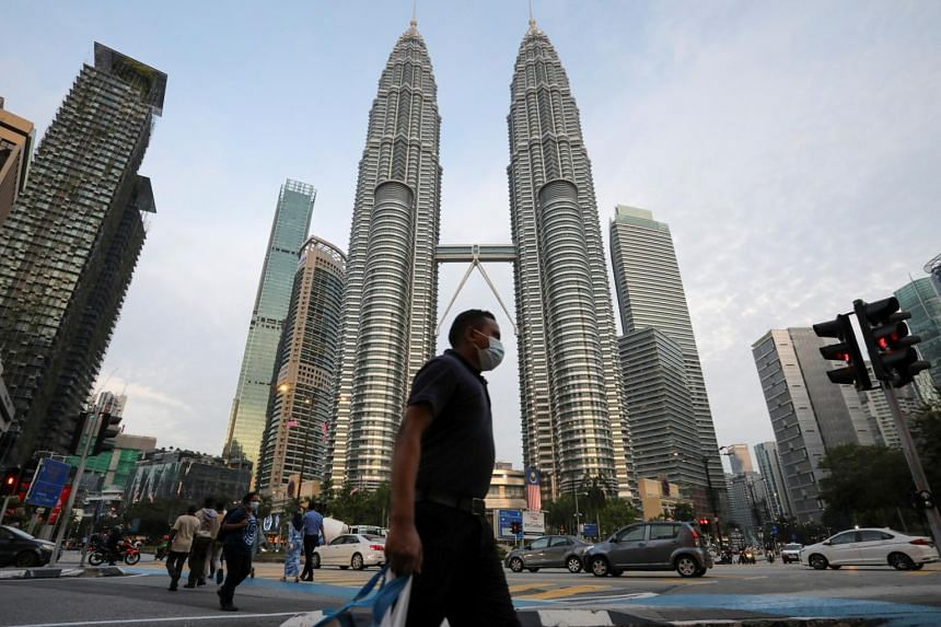 A man crosses a street in front of Petronas Twin Towers in Kuala Lumpur on Aug 11, 2020.