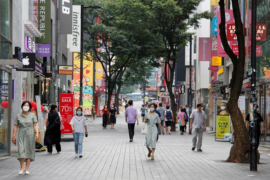 People wearing masks walk at Myeongdong shopping district in Seoul on Aug 19, 2020.