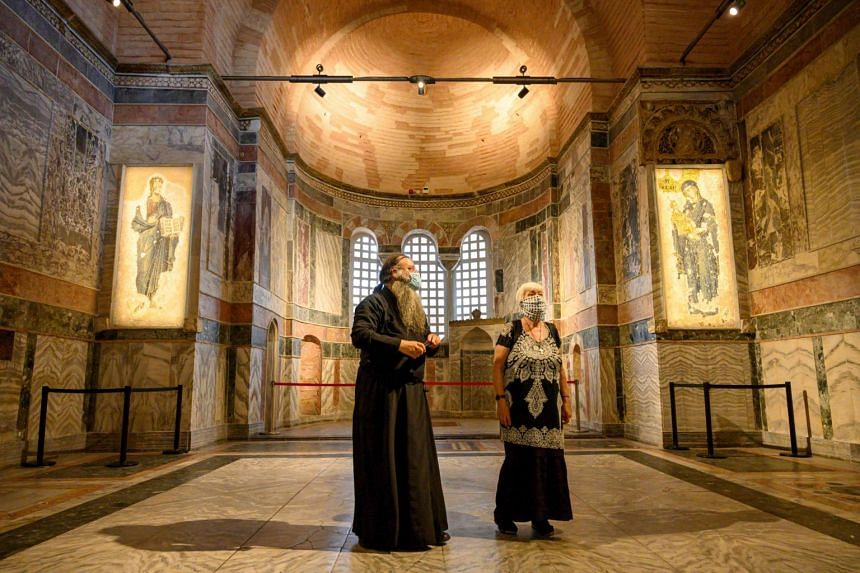 A priest (left) and a woman visit the Chora museum in Istanbul on Aug 21, 2020.