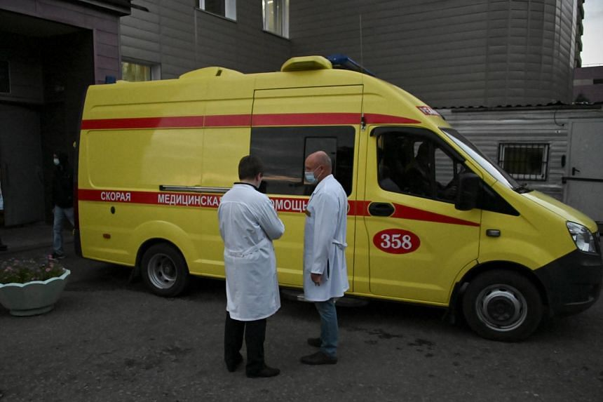 Medical specialists stand next to an ambulance transporting Russian opposition leader Alexei Navalny to an airport before his medical evacuation to Germany on Aug 22, 2020.