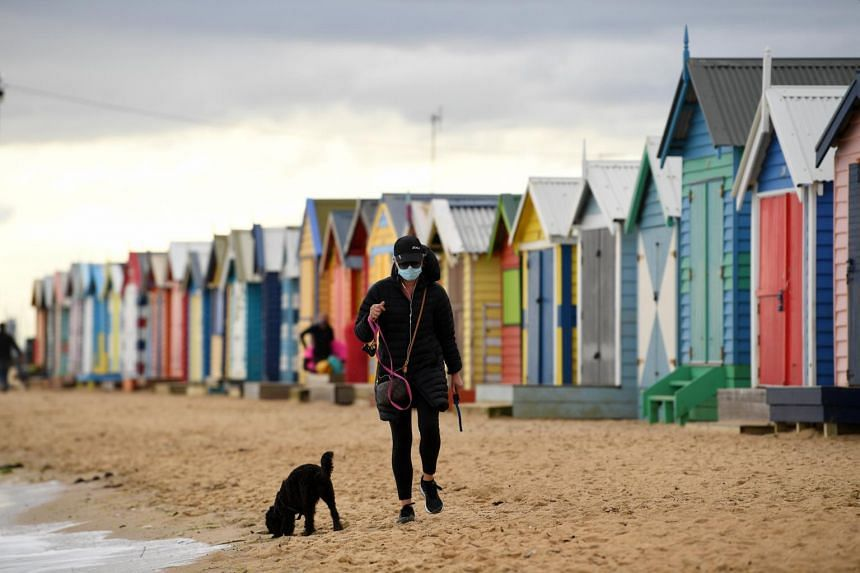 A woman walks her dog on Brighton beach in Melbourne, on Aug 20, 2020.
