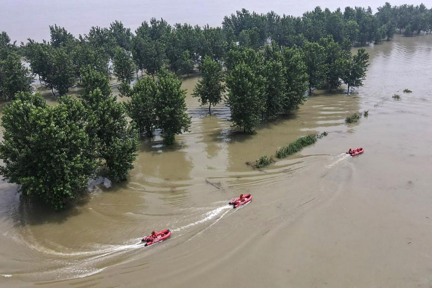 Firefighters patrol at a flooded area near the Yangtze river in Zhenjiang, China, on July 20, 2020.