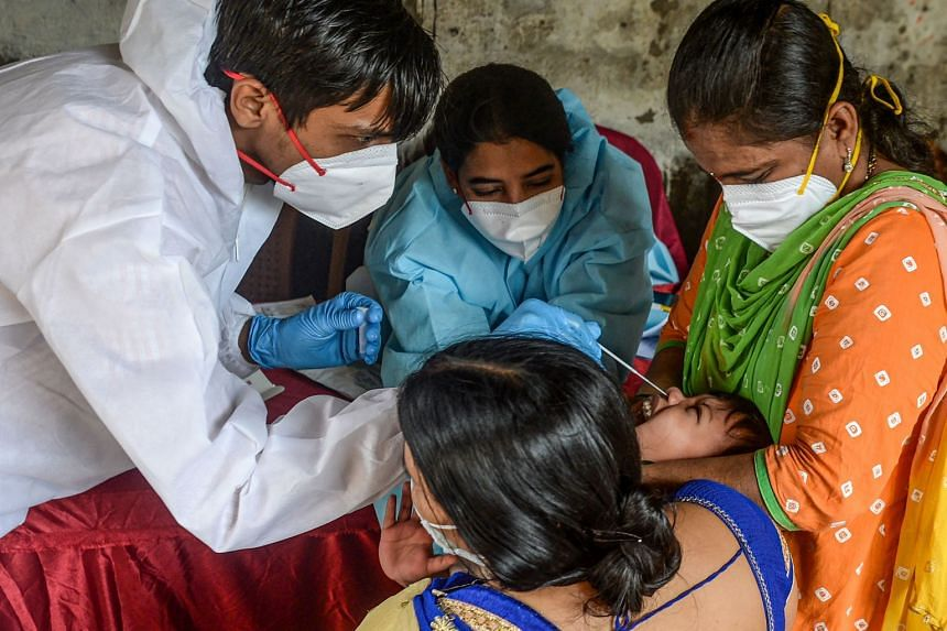 A health worker collects a nasal swab from a child as others restrain him in Mumbai on Aug 19, 2020.