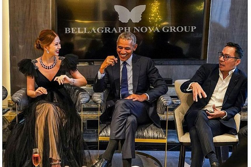 ALLEGEDLY PHOTOSHOPPED: BN Group co-founder Evangeline Shen with Mr Barack Obama at a charity event here last December with the firm's name and logo on the screen, and co-founder Terence Loh to Mr Obama's left.