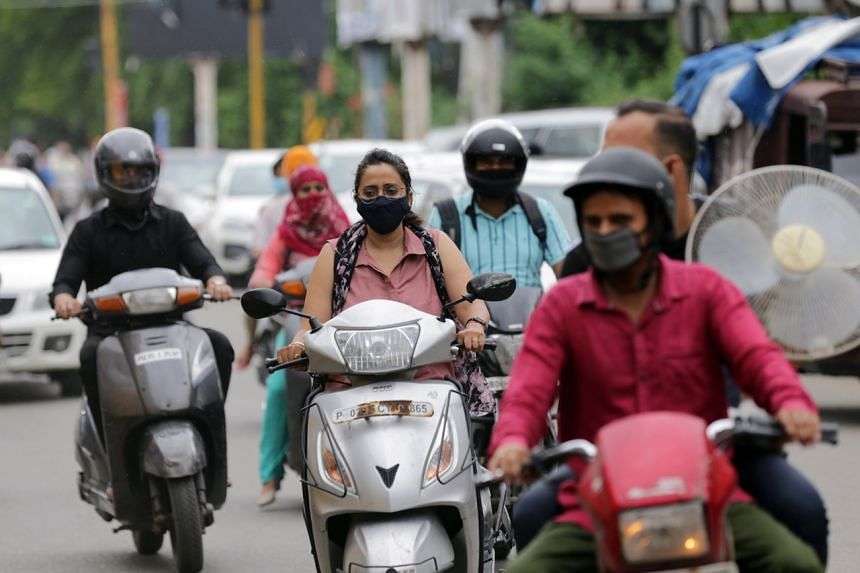 Commuters wearing face masks ride on a busy road in Amritsar, India, on Aug 21, 2020.