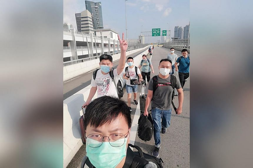 Some of the 10 Malaysian staff employed by Gain City walking across the Causeway last Monday when the border reopened. They are serving seven-day, stay-home notices and will start work if their swab test results come back negative.