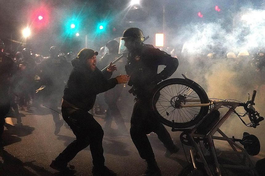 A police officer ripping a bicycle from a protester in front of the Multnomah County Sheriff's Office on Saturday in Portland, Oregon. Hundreds of protesters clashed with police following a rally in the city. President Donald Trump took a jibe at his