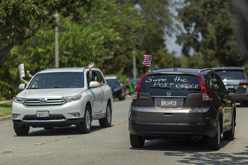 Protesters rallying outside the home of US Postal Service Board of Governors member John M. Barger in San Marino, California, to decry recent operational changes that could affect the processing of mail-in ballots for November's presidential election
