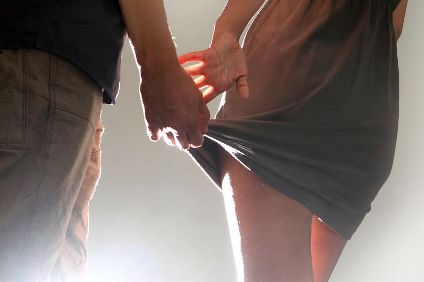 Posed photo of a man pulling a woman's skirt.